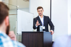 Smiling businessman standing at tribune in conference hall Stock Images