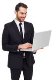 Smiling businessman standing and using laptop. On white background Royalty Free Stock Image
