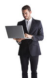 Smiling businessman standing using laptop. On white background Stock Photo