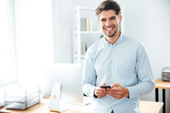 Smiling businessman standing and using mobile phone in office Royalty Free Stock Photography