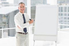 Smiling businessman standing at whiteboard with marker Royalty Free Stock Image