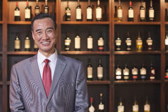 Smiling Businessman Standing by Wine Bottles, Portrait Royalty Free Stock Images