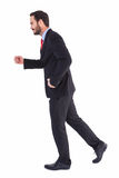 Smiling businessman stepping with hands raised Stock Photos