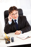 Smiling businessman straightening eyeglasses Stock Image