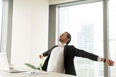 Smiling businessman stretching at workplace in modern office. royalty free stock images
