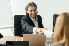 Smiling businessman in suit handshaking female partner at group. Smiling businessman in suit handshaking greeting businesswoman at group negotiation, friendly Royalty Free Stock Photography