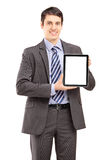 Smiling businessman in suit showing a tablet Stock Photos