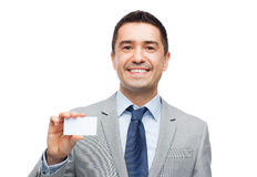 Smiling businessman in suit showing visiting card. Business, people and office concept - smiling businessman in suit showing blank white visiting card Royalty Free Stock Photography