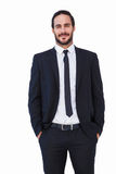 Smiling businessman in suit standing with hands in pockets. On white background Stock Photo
