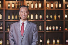 Smiling businessman in a suit standing by a wall with wine bottles, Portrait Royalty Free Stock Images