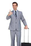Smiling businessman with suitcase showing his thumb up Royalty Free Stock Images