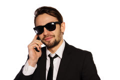 Smiling businessman in sunglasses on his mobile Stock Photos