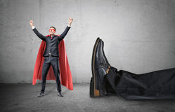 A smiling businessman in a superhero red cape with hands raised in success motion standing beside a giant human foot. Stock Photography