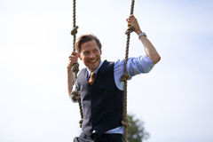 Smiling businessman swinging in ropes Stock Photo