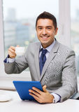 Smiling businessman with tablet pc and coffee cup Stock Photography
