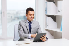 Smiling businessman with tablet pc and coffee cup Royalty Free Stock Photos