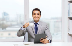 Smiling businessman with tablet pc and coffee cup Stock Images