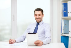 Smiling businessman with tablet pc and documents Royalty Free Stock Images