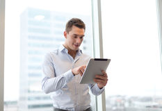 Smiling businessman with tablet pc in office Royalty Free Stock Photo
