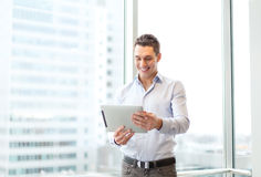 Smiling businessman with tablet pc in office Stock Images