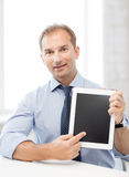 Smiling businessman with tablet pc in office Royalty Free Stock Photography