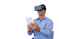 Smiling businessman with tablet sitting on chair while using vr glasses Royalty Free Stock Photo