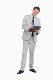 Smiling businessman taking notes. Against a white background Stock Image