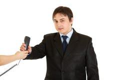 Smiling businessman taking phone from secretary Stock Photos