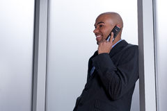 Smiling businessman talking on his cell phone. Smiling businessman beside an office window, talking on his cell phone Royalty Free Stock Photo