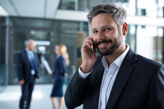 Smiling businessman talking on mobile phone in office corridor Stock Photography