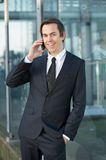 Smiling businessman talking on mobile phone outdoors Royalty Free Stock Photos