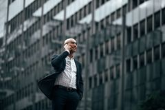 Businessman standing outdoors talking over mobile phone Stock Photos