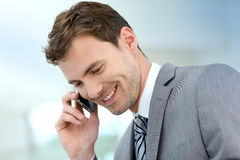Smiling businessman talking on the phone. Smiling businessman having a phonecall in building hallway Stock Photography