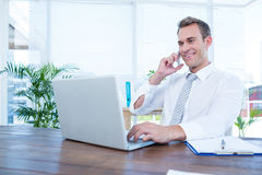Smiling businessman talking on the phone. In the office Royalty Free Stock Image