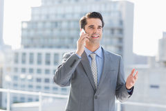 Smiling businessman talking on the phone. At the patio Stock Photo
