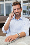 Smiling businessman talking on phone using his laptop. In patio of restaurant Stock Photo