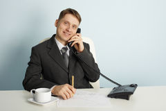 Smiling businessman in talks on phone Stock Photography