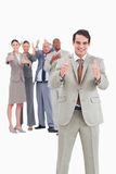 Smiling businessman with team behind him. Giving thumbs up against a white background Royalty Free Stock Photos