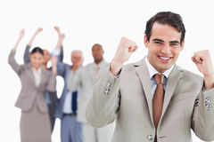 Smiling businessman with team behind him raising fists Royalty Free Stock Image