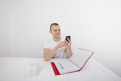 Smiling businessman text messaging on cell phone at desk Royalty Free Stock Image
