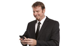 Smiling businessman texts on cell phone Stock Image
