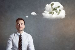 Smiling businessman thinking of money. Man with eyes closed and a light smile. A thought bubble is depicting a couple of dollar bills Royalty Free Stock Photos