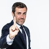 Smiling businessman for time in management or self-confident leadership. Smiling good-looking young  man showing one finger to hold on, listen or wait for time Stock Photos
