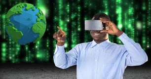 Smiling businessman touching low poly earth while using VR glasses. Digital composite of Smiling businessman touching low poly earth while using VR glasses Stock Photography