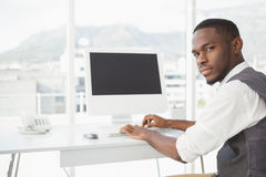 Smiling businessman tying on keyboard Stock Photo