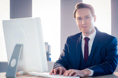 Smiling businessman typing on laptop and looking at camera Stock Photography