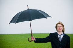 Smiling businessman with umbrella Stock Images