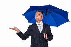 Smiling businessman under umbrella with hand out Stock Images