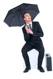 Smiling businessman under umbrella sitting on cube Stock Images