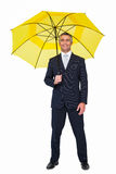 Smiling businessman under yellow umbrella Royalty Free Stock Images